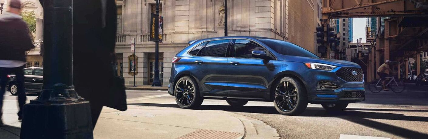 side profile of blue 2019 Ford Edge rounding corning in a city