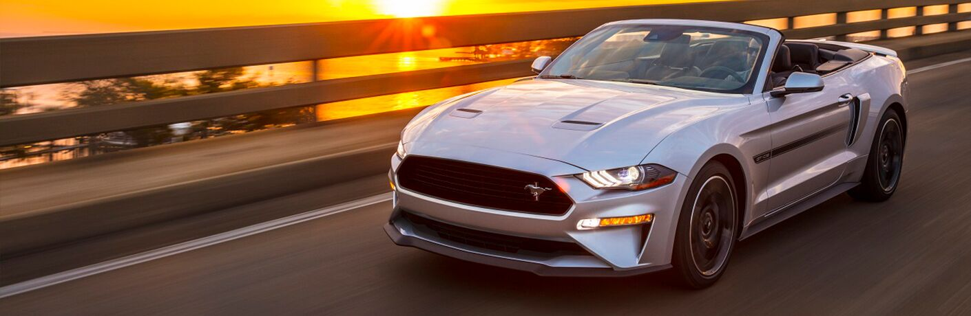 silver 2019 Ford Mustang convertible driving by the ocean at sunset
