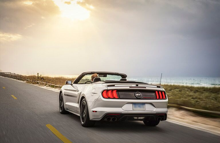 rear view of silver 2019 Ford Mustang convertible driving by ocean