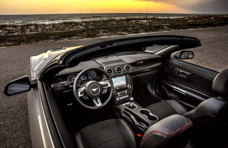 dashboard and front seat in 2019 Ford Mustang convertible with sunset in background