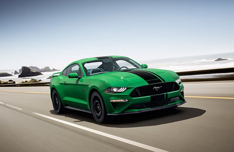 green 2019 Ford Mustang with black racing stripe driving by ocean