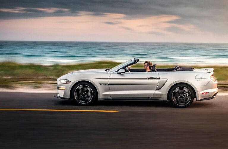 side profile of silver 2019 Ford Mustang driving by ocean