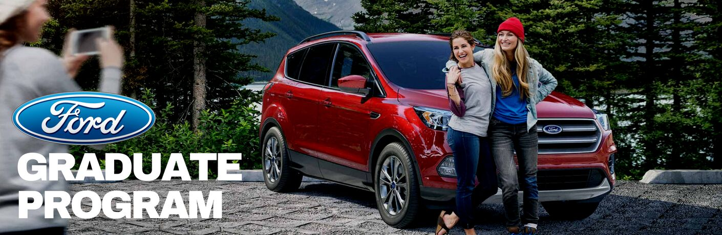 two_young_women_posing_for_a_picture_in_front_of_red_Ford_crossover_with_Ford_Graduate_Program_title