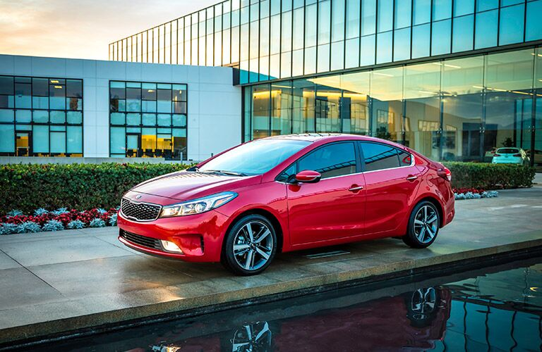 Profile view of red 2019 Kia Forte parked in front of water