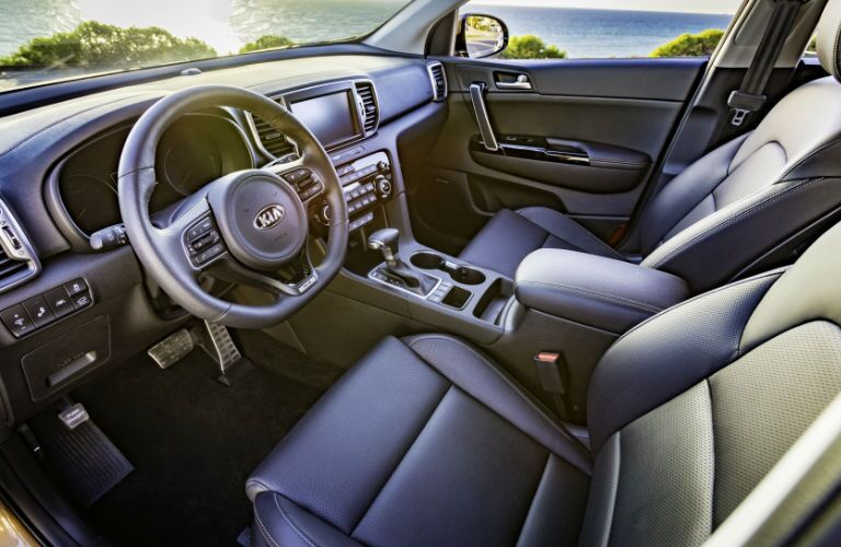 side view of front interior of 2018 kia sportage including seats, steering wheel and center console