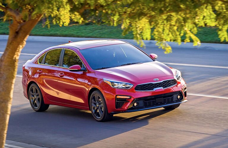 Red 2019 Kia Forte driving on parkway