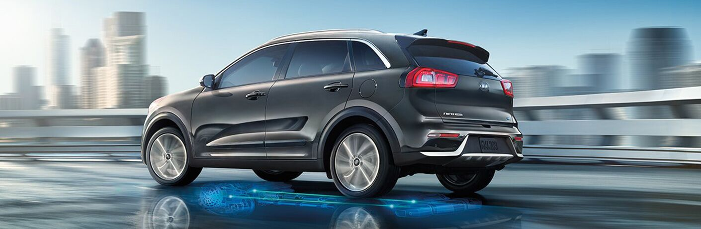 Profile view of black 2019 Kia Niro with city skyline in the background