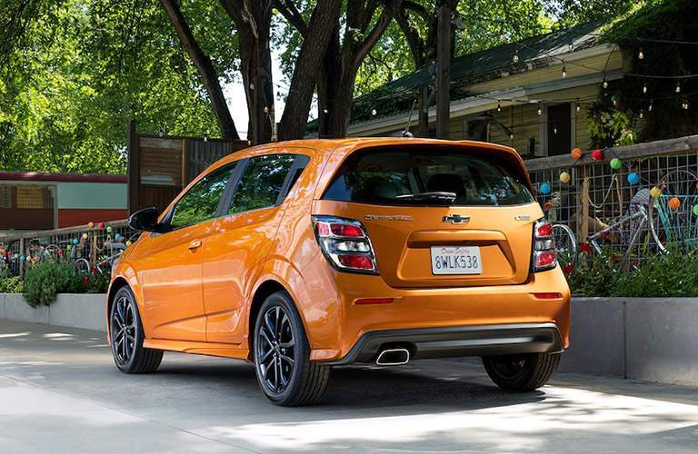 Rear profile of the 2018 Chevrolet Sonic parked by a wall by many bikes