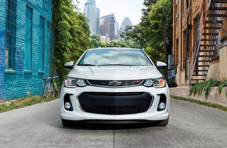 Front grille and headlights of the 2018 Chevrolet Sonic parked between tow brick buildings