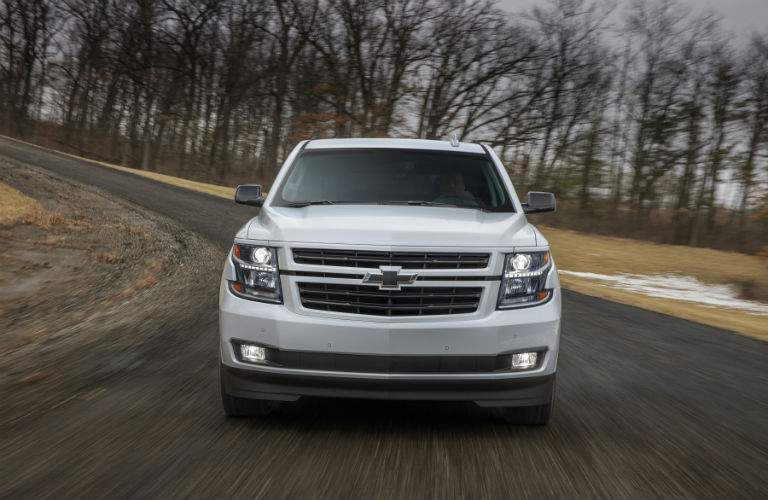 head-on view of the 2018 Chevrolet Tahoe driving on a curving road by bare trees
