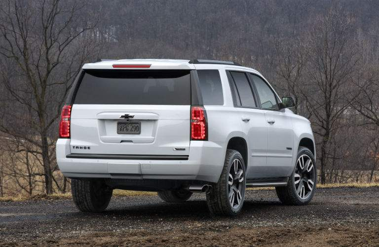 Rear Profile of the 2018 Chevrolet Tahoe parked on a gravel road by bare trees