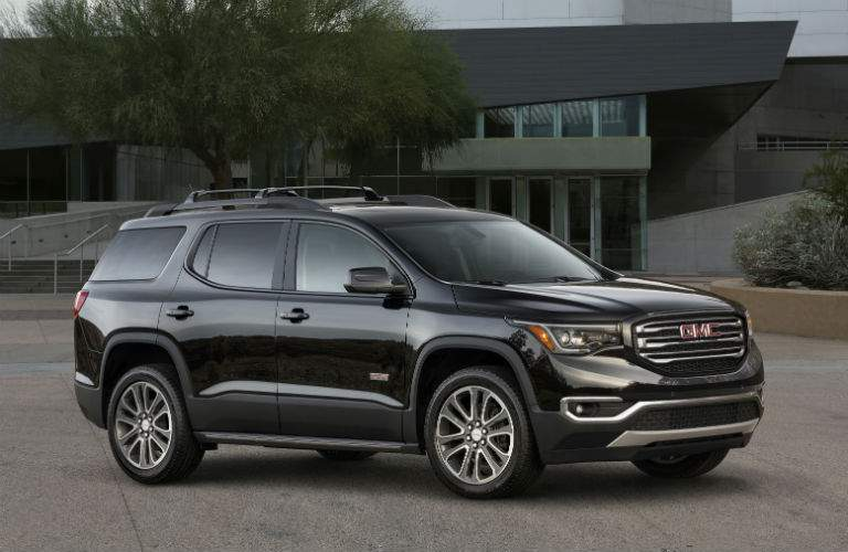 Front quarter turn profile of the 2018 GMC Acadia in front of a modern building and trees
