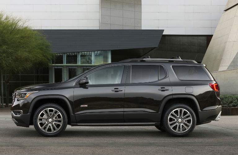 Side profile of the 2018 GMC Acadia in front of a modern building and trees