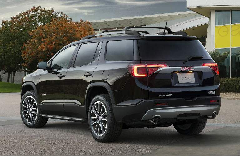 Rear profile of the 2018 GMC Acadia in front of a modern building and trees