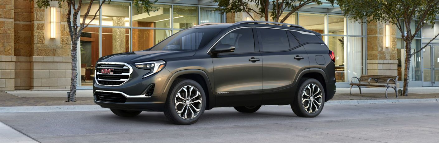 2018 GMC Terrain profile parked on a street by a row a trees and a bench, in front of a modern building
