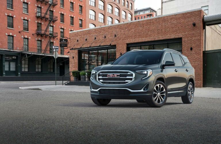 Front Quarter Profile of the 2018 GMC Terrain in front of a squat brick building