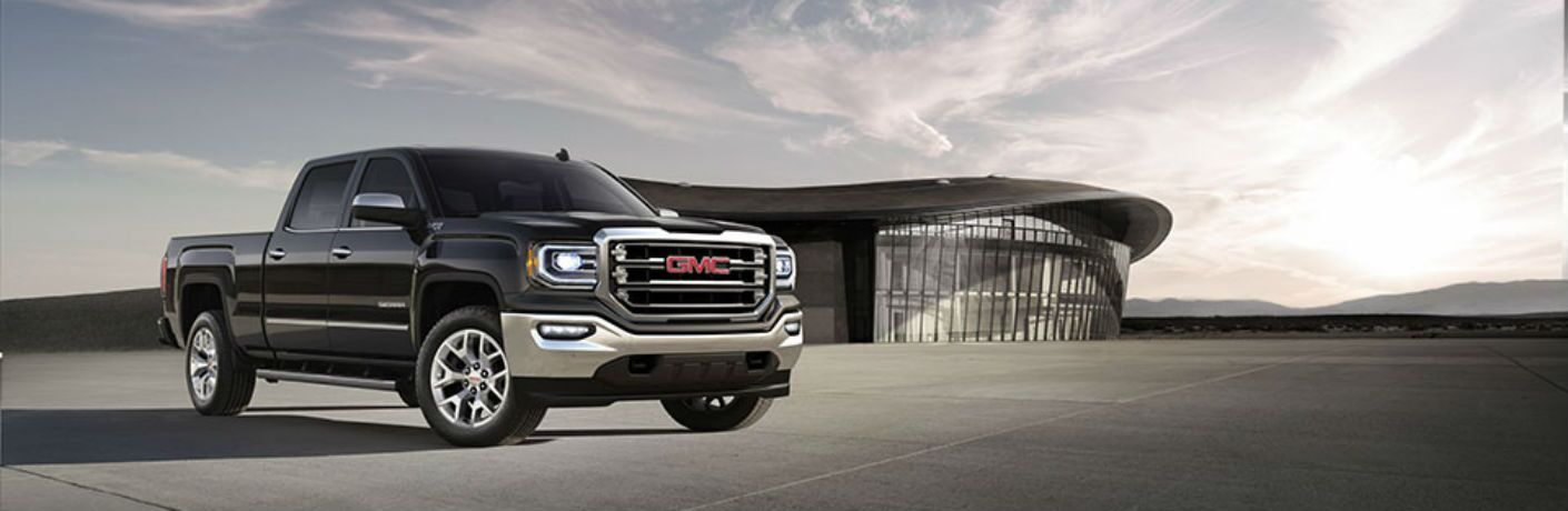 Front quarter profile of the 2018 GMC Sierra 1500 parked on an open lot in front of a  modern looking building