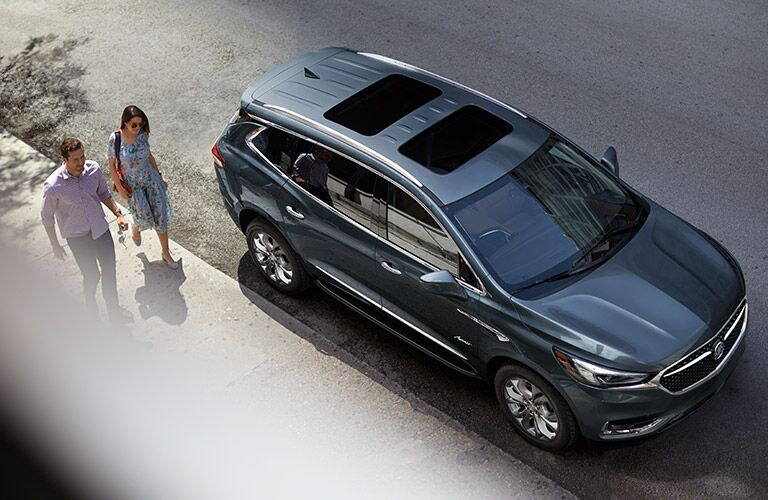 2019 Buick Enclave exterior top view with front fascia and passenger side two people walking on sidewalk next to it
