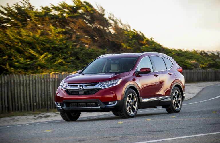 Exterior view of a red 2018 Honda CR-V parked on a road with trees in the background