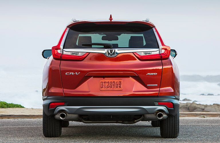 Exterior view of the rear of a red 2019 Honda CR-V parked on an ocean-side highway