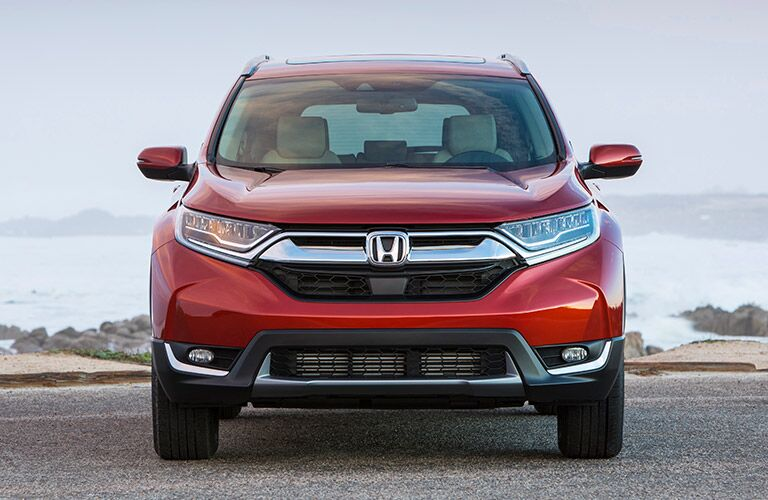 Exterior view of the front of a red 2019 Honda CR-V parked on an ocean-side highway