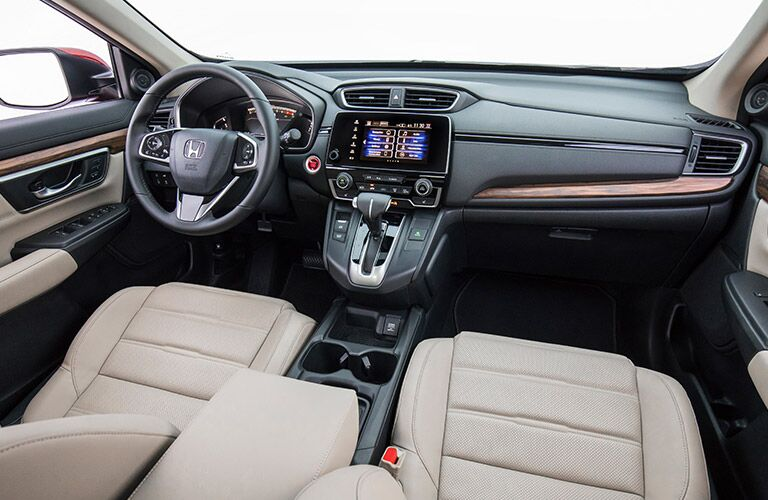 Interior view of the black steering wheel, touchscree, and beige seating inside a 2019 Honda CR-V