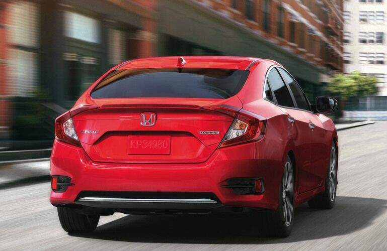 Exterior view of the rear of a red 2019 Honda Civic driving down a city street