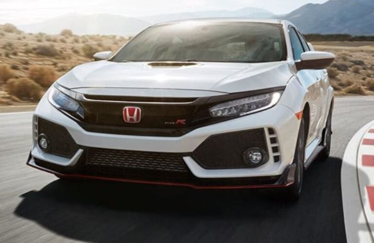 Exterior view of the front of a white 2019 Honda Civic Type R driving around a race track