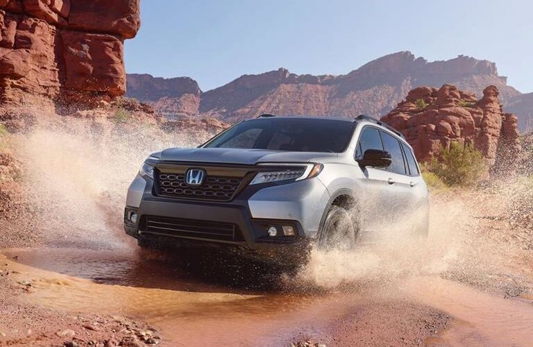 Exterior view of a silver 2019 Honda Passport driving through mud