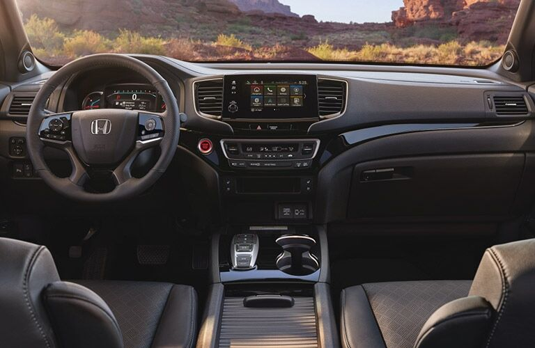 Interior view of the steering wheel and front seating area inside a 2019 Honda Passport