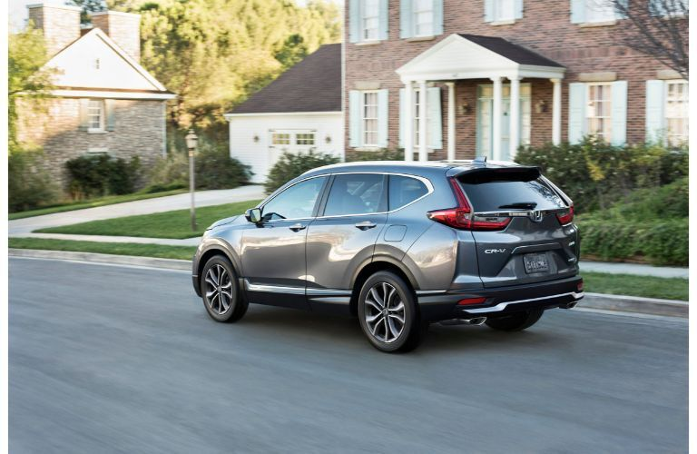2020 Honda CR-V Touring grey daytime driving in front of brick house with pillars clpb