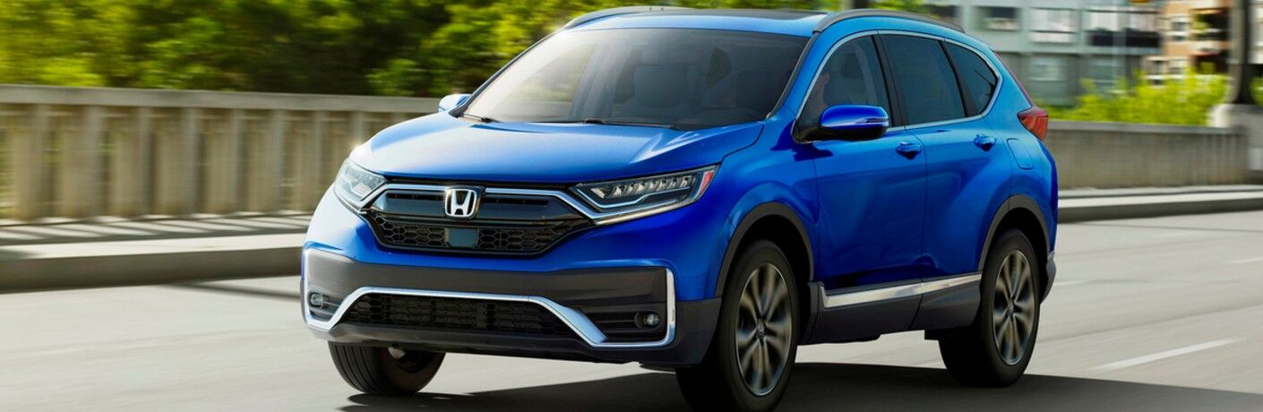 2020 Honda CR-V blue exterior shot driving over bridge view of front and driver side