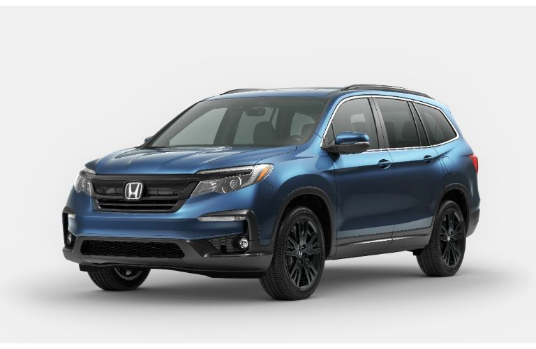 2021 Honda Pilot Elite blue parked on sand in front of mountain