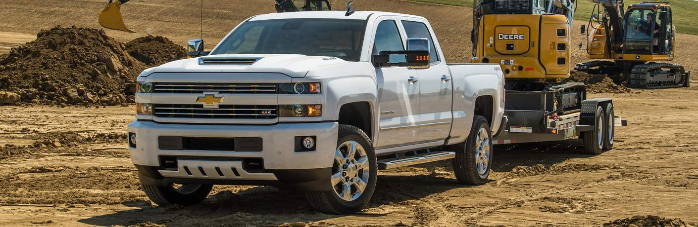 2018 Chevy Silverado 2500HD white front view towing construction equipment