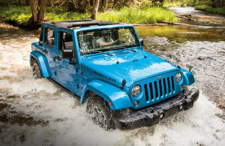 man driving blue 2018 Jeep Wrangler JK through a river