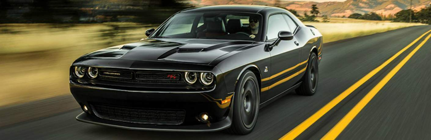 man driving a Dodge Challenger in black