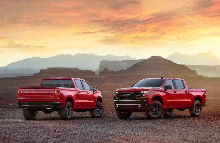 two red 2019 Chevy Silverado 1500 models parked in the desert