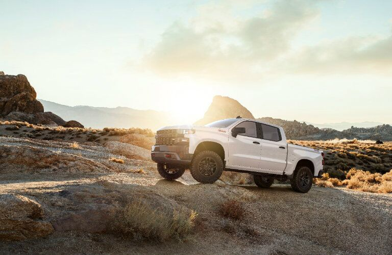 white 2019 Chevy Silverado 1500 driving on rocky terrain at sunset
