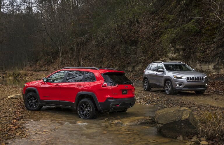 red and silver 2019 Jeep Cherokee models parked in the wilderness