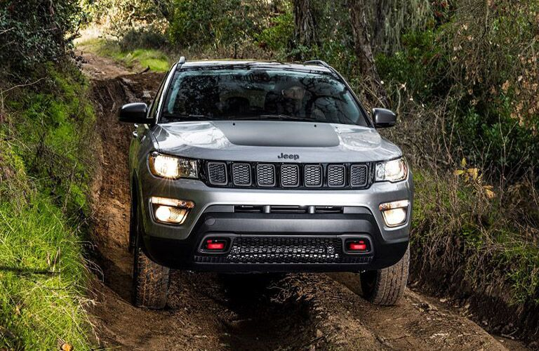 Front view of 2019 Jeep Compass driving through wooded area