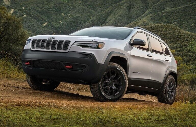 Front driver angle of a white 2019 Jeep Cherokee parked outdoors on a slight slope