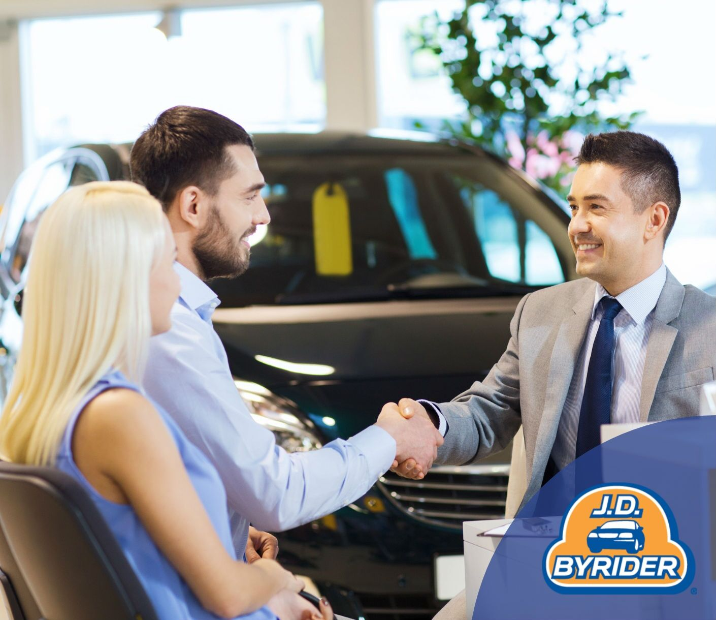 couple shaking hands with car salesman with J.D. Byrider logo in the corner