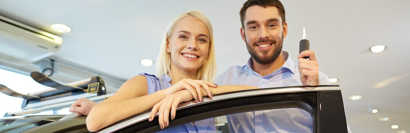couple standing behind car door smiling and holding up car key