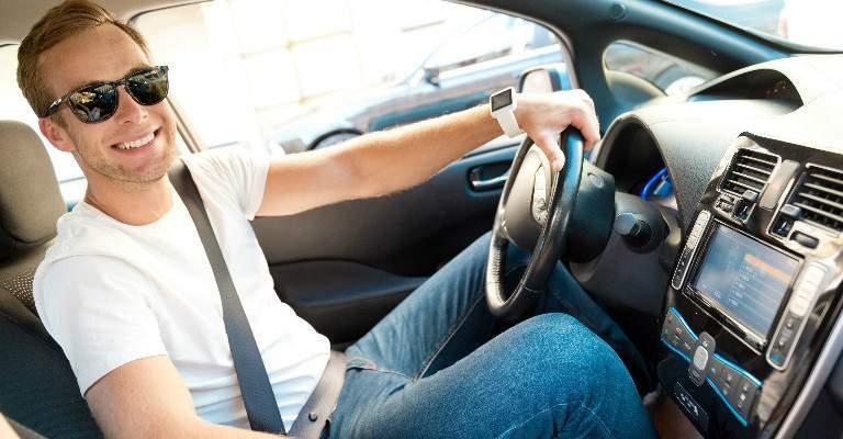 man wearing sunglasses while driving car and looking at camera
