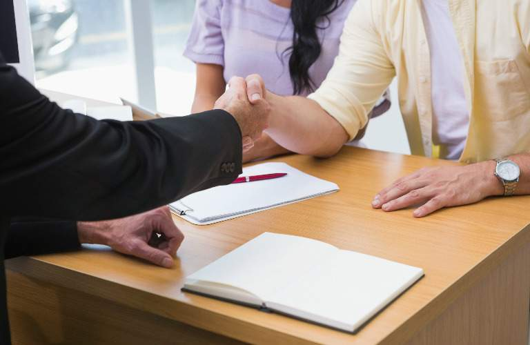 salesperson shaking hands with a couple as paperwork is signed