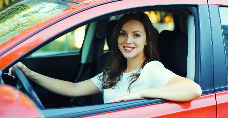 woman in red car smiling at camera