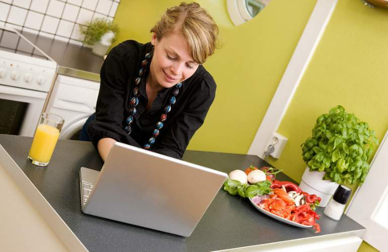 woman in kitchen looking at computer