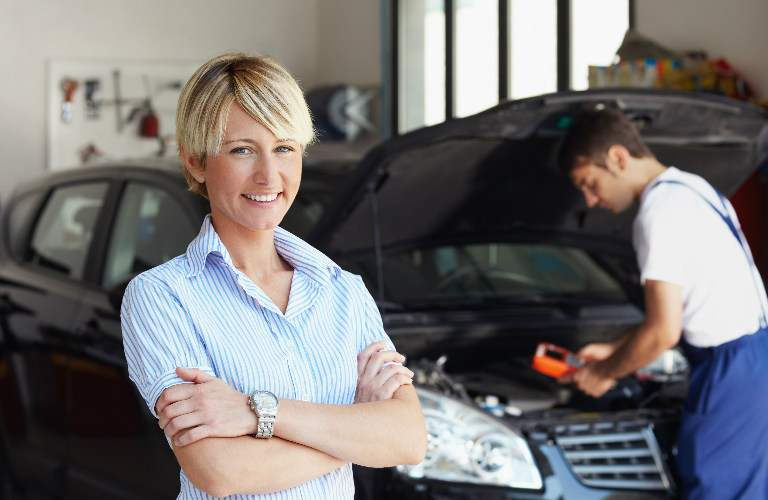 woman standing in front of mechanic working on her car