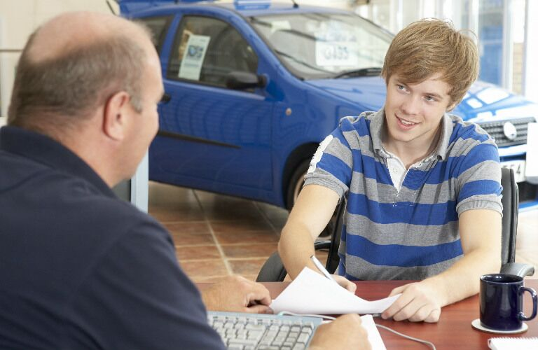young man in auto dealership filling out paperwork
