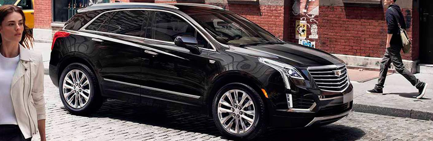 Black Cadillac XT5 stopped for pedestrians on a busy city street